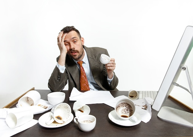 Young man drinking a lot of coffee, but can't wake up and work anyway. keep sleeping at the office. concept of office worker's troubles, business, problems and stress. Free Photo