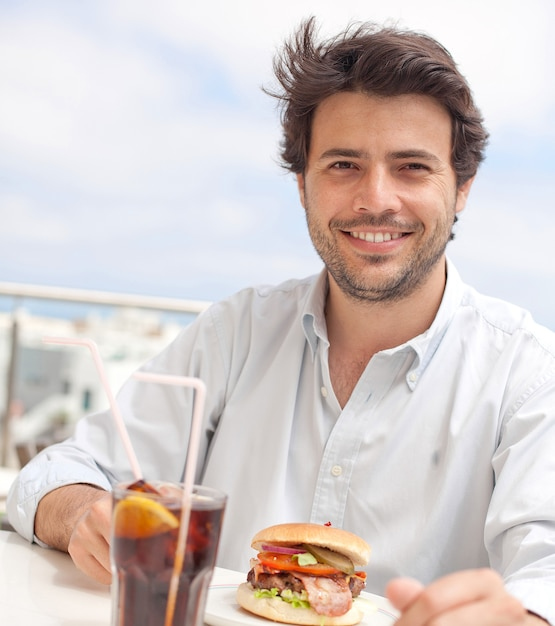 Young man eating a hamburguer Premium Photo