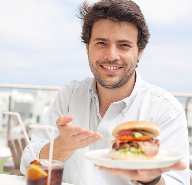 Young man eating a hamburguer Premium Photo