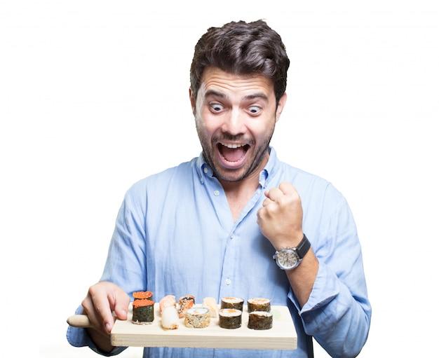 Young man eating sushi on white background Premium Photo