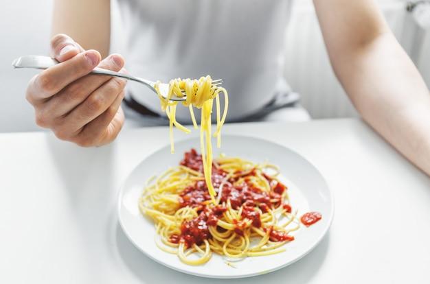 Молодой человек ест вкусные спагетти с томатным соусом. крупный план. Бесплатные Фотографии