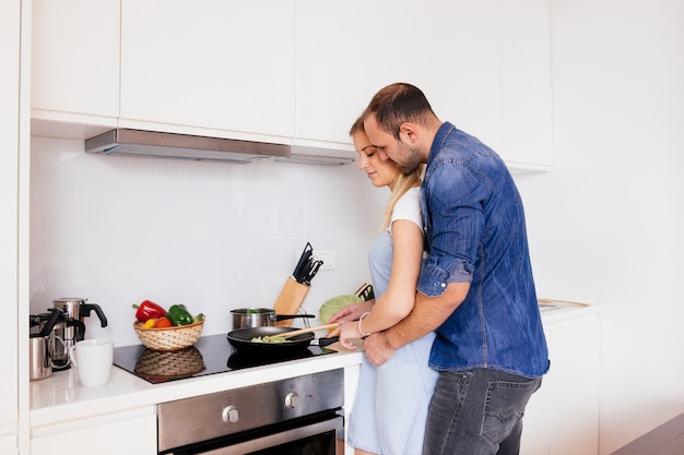 Young man embracing his wife preparing food in the kitchen Free Photo