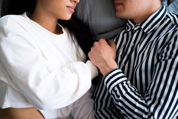 Young man and ethnic woman lying on bed and holding hands Free Photo