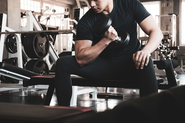 Young man exercising building muscles at the gym Premium Photo