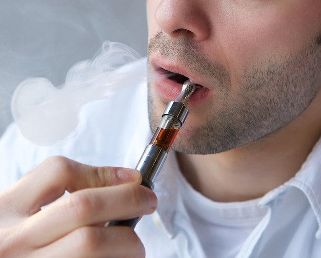 Young man exhaling smoke from electric cigarette Premium Photo