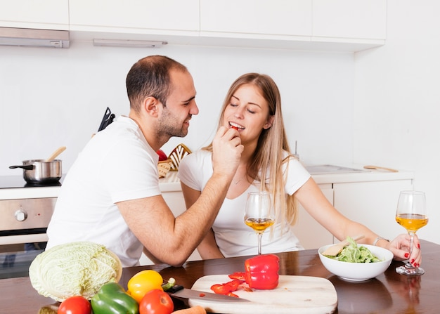 Young man feeding bellpepper to her wife with wineglasses on wooden table Free Photo