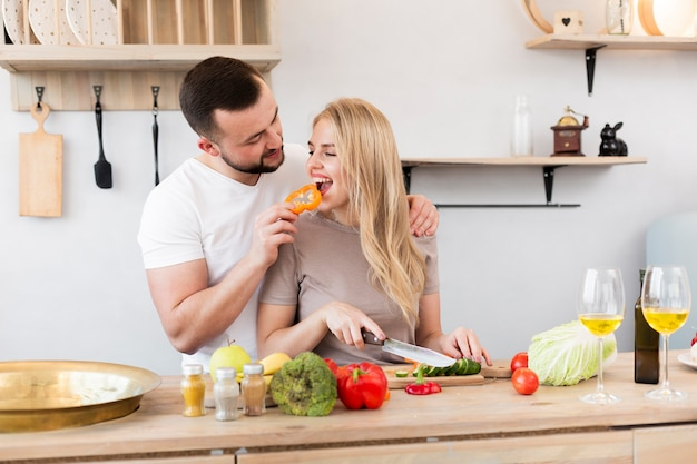 Young man feeding his woman with bell pepper Free Photo