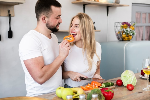 Young man feeding the woman with bell pepper Free Photo