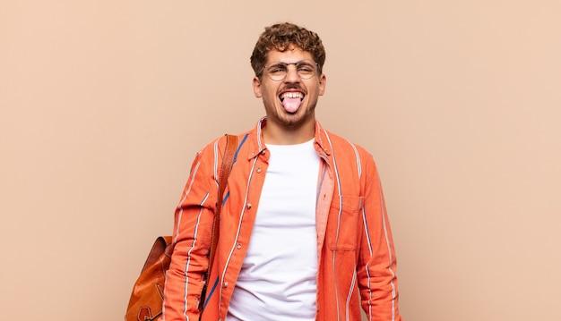 嫌悪感とイライラを感じ、孤立した舌を突き出している若い男 Premium写真