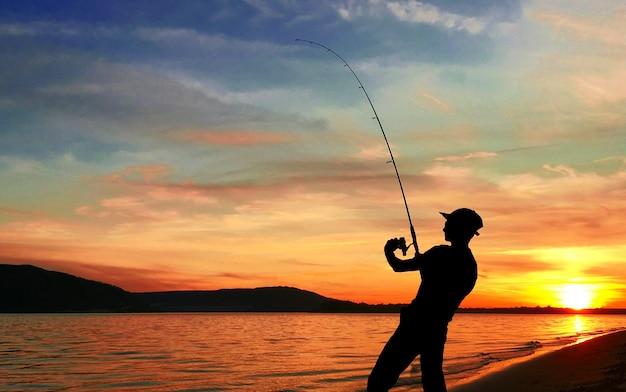 日没時に湖で釣りをする若い男 Premium写真