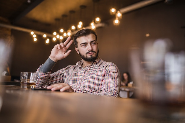Young man gesturing while drinking alcohol at bar Free Photo