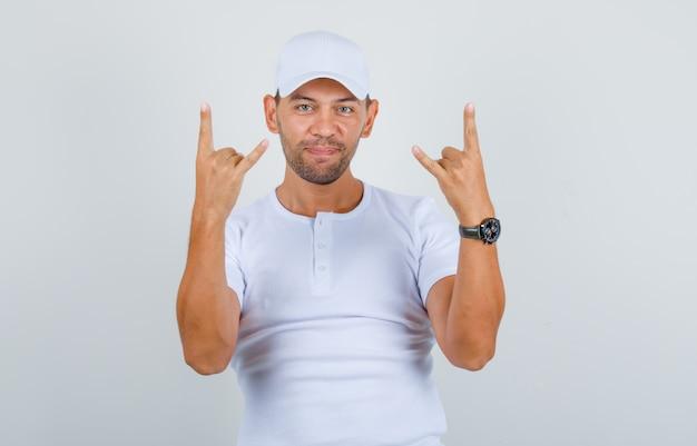 Молодой человек жестикулирует пальцами как рэпер в белой футболке, кепке и выглядит позитивно, вид спереди. Бесплатные Фотографии