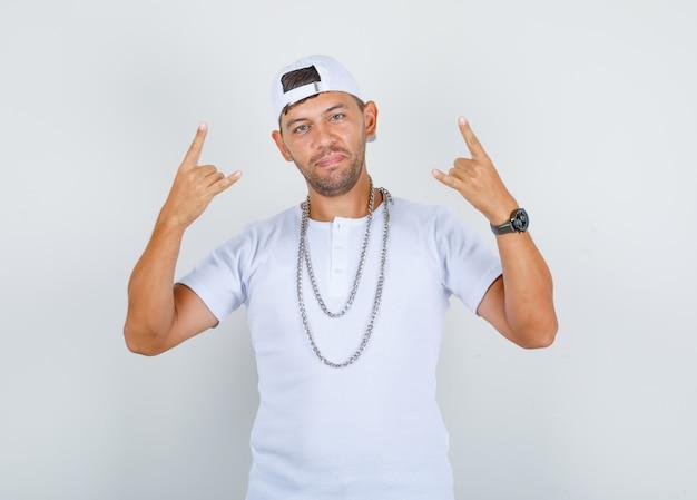 Молодой человек жестикулирует пальцами как рэпер в белой футболке, кепке, цепном ожерелье и выглядит позитивно, вид спереди. Бесплатные Фотографии