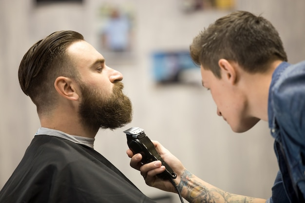 Young man getting beard grooming at barbershop Free Photo