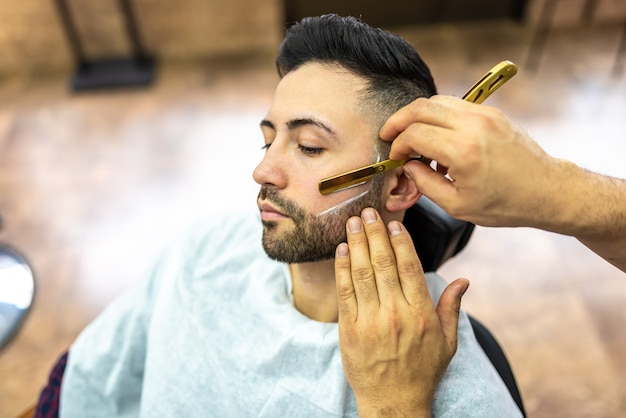 Young man getting a beard shaved Premium Photo