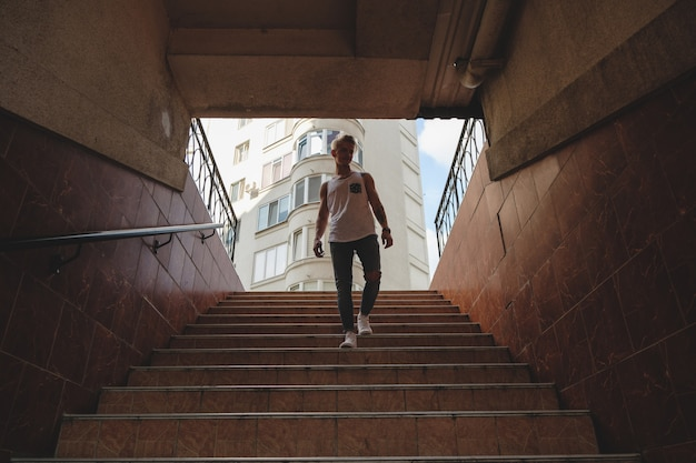 Young man getting down stairs in pedestrian subway Free Photo