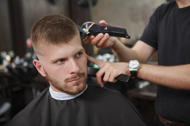 Young Man Getting New Haircut At Barbershop Premium Photo