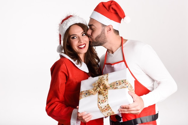 Young man giving a christmas gift to his woman with a kiss Photo ...