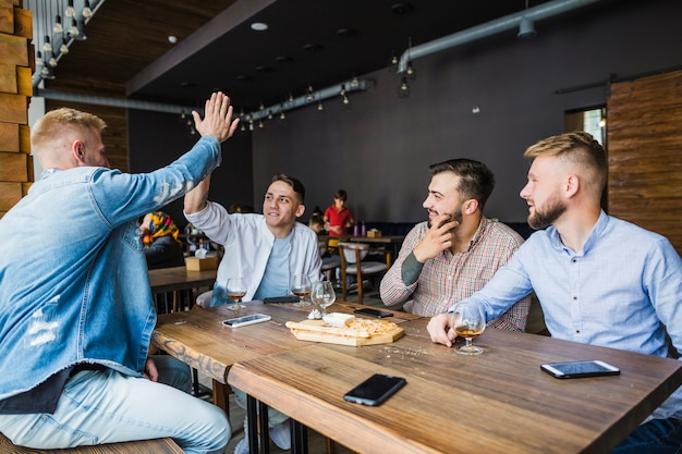 Young man giving high five to his friends in the restaurant Free Photo