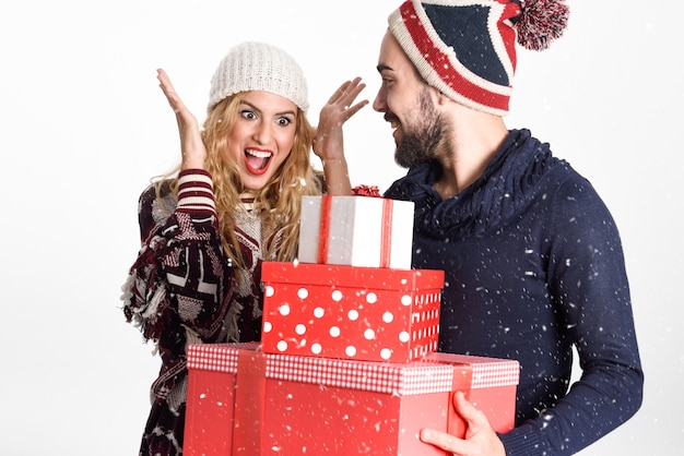 young man giving many christmas gifts to his woman dresses with winter clothes on white