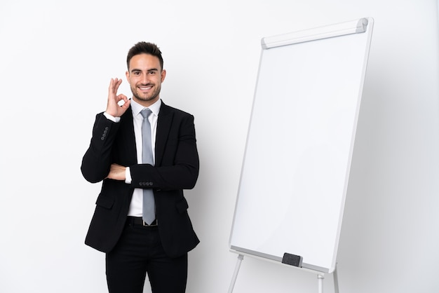 Young man giving a presentation on white board and showing ok sign with fingers Premium Photo