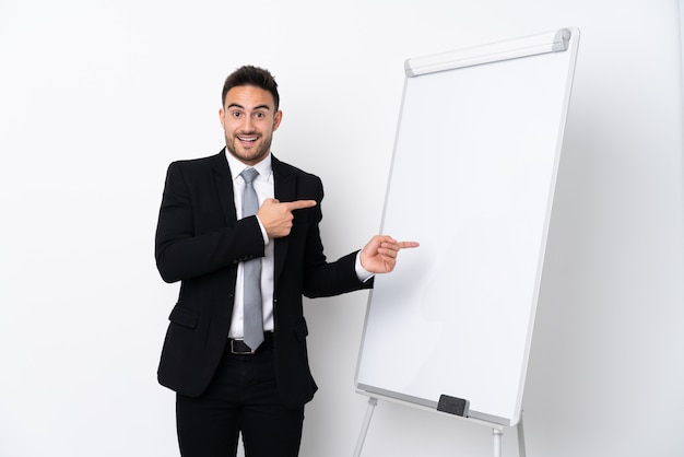 Young man giving a presentation on white board and surprised while pointing side Premium Photo