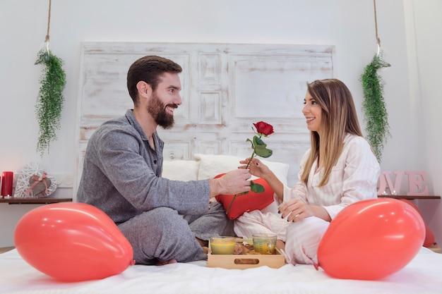 침대에 여자에 게 빨간 장미를주는 젊은 남자 무료 사진