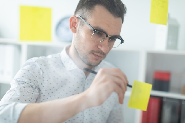 A young man in glasses stands near a board with stickers and writes them with a pencil. Premium Photo