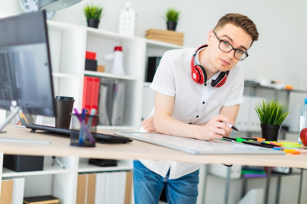A young man in glasses stands near a computer desk. a young man draws a marker on a magnetic board. on the neck, the guy's headphones hang. Premium Photo