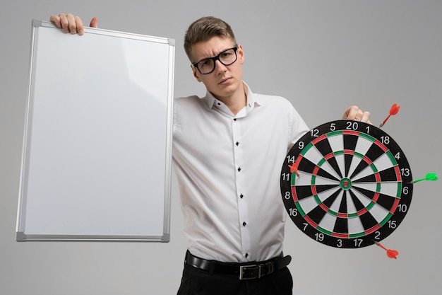 Young man in glasses with target with dart not in center and empty plate in his hands on white Premium Photo