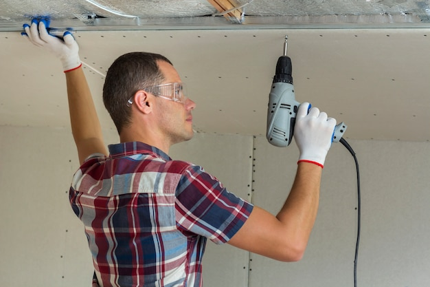 Young man in goggles fixing drywall suspended ceiling to metal frame using electrical screwdriver on ceiling. Premium Photo