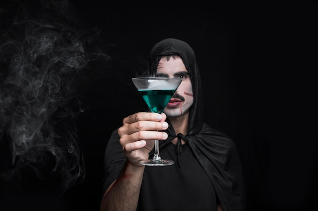 Young man in halloween cloak posing in studio with beverage Free Photo