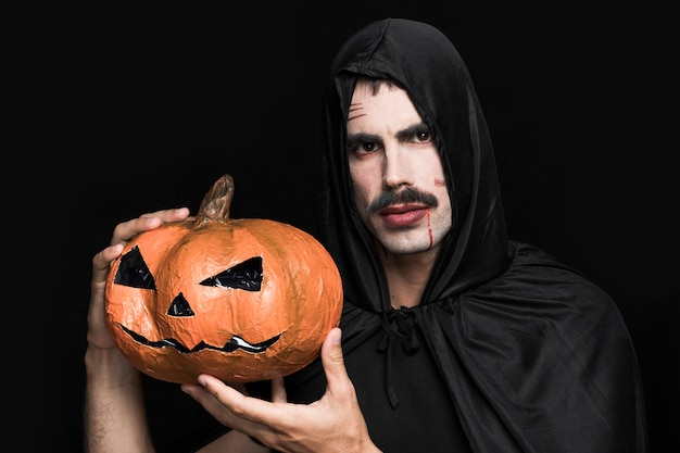 Young man in halloween costume holding decorative pumpkin Free Photo