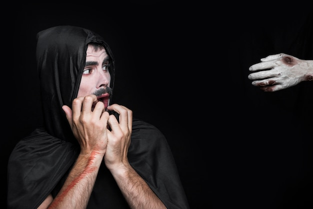 Young man in halloween costume looking at corpse hand Free Photo