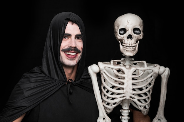 Young man inhalloween costume posing in studio with skeleton Free Photo