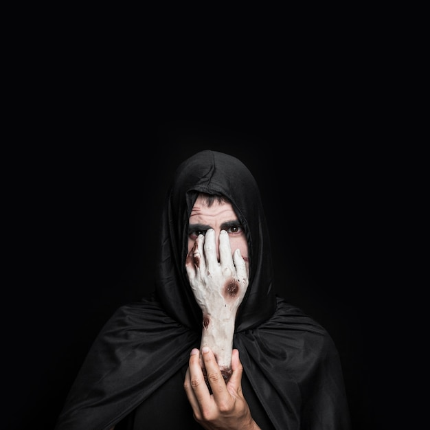 Young man in halloween costume with hood holding corpse hand Free Photo