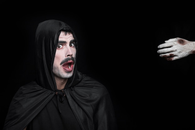 Young man in halloween costume with scared face and hand of corpse Free Photo