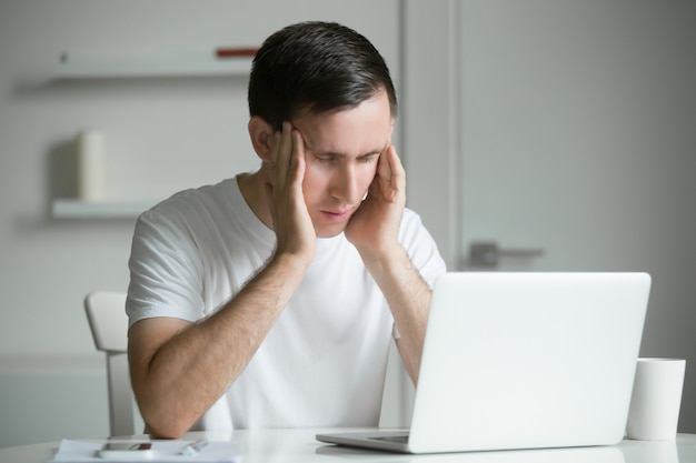 Young man, hands at his temples, at the white desk, laptop near Free Photo