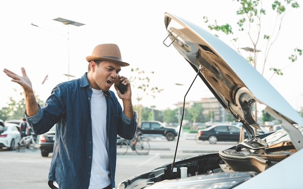 Young man has driven a car and broke down on the way Premium Photo