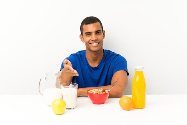 テーブルハンドシェイクで朝食を持っている若い男 Premium写真