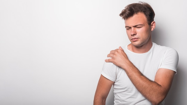 Young man having pain shoulder against white background 23 2147889141