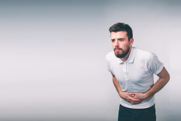 Young man having a stomachache..close up of male body isolated on white wall Premium Photo