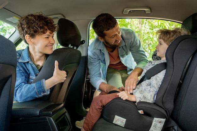 彼と彼のかわいい妻が車の後部座席で男の子を見ている間、彼の愛らしい幼い息子がシートベルトを締めるのを手伝っている若い男 Premium写真