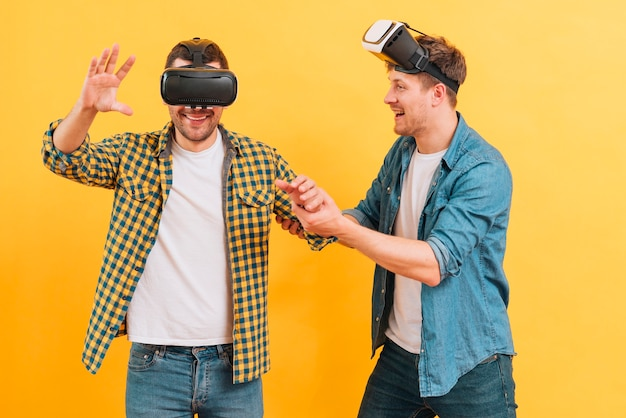 Young man helping his friend wearing glasses of virtual reality against yellow background Free Photo