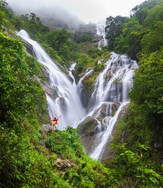 Молодой человек, походы возле водопада Premium Фотографии