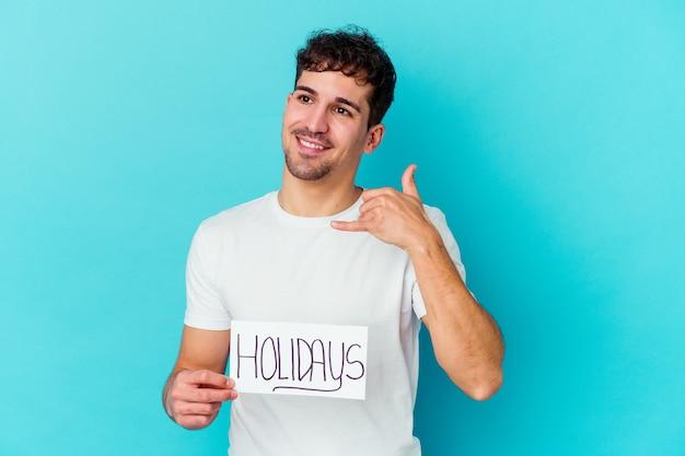 指で携帯電話の呼び出しジェスチャーを示す分離された休日のプラカードを保持している若い男 Premium写真