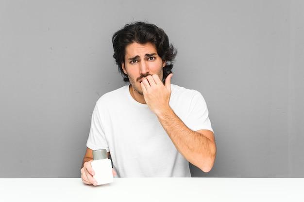Молодой человек держит крем после бритья, кусая ногти, нервный и очень взволнованный. Premium Фотографии
