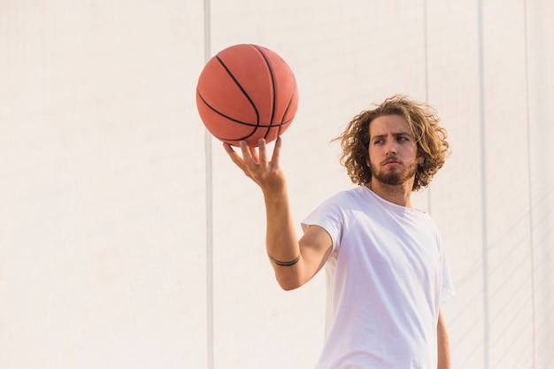 Young man holding basketball against wall Free Photo