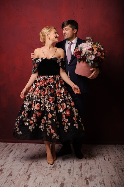 Young man holding a bouquet of flowers hugging his woman Premium Photo