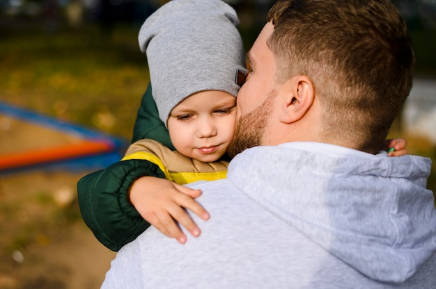 Young man holding a boy in his arms Free Photo
